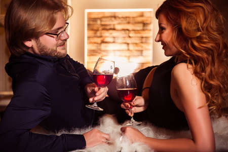 furs: Couple relaxing with glass of red wine at romantic fireplace on winter evening time. Smiling and looking at each other. Image toned. Horizontal