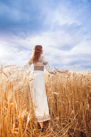 Pretty woman wearin? a embroidered dress with braid walking to the camera among of golden field and pushes wheat. Photo from behind Stock Photo