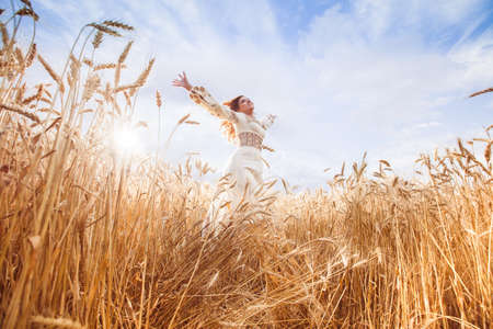 embroidered: Beauty girl dressed in embroidered blouse jump under wheat field
