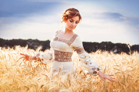 Pretty woman dressed in embroidered clothes with braid standing among of wheat field and looking down