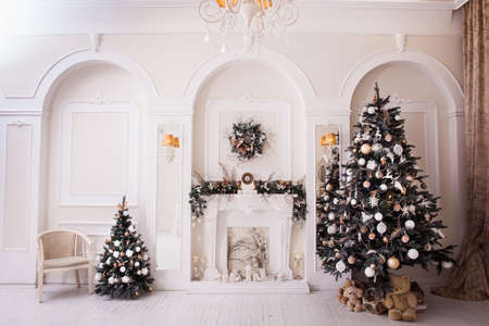 baroque room: Winter New Year and Christmas decoration in white large living room. Decorated Christmas tree near baroque sofa in classical hall. Stock Photo