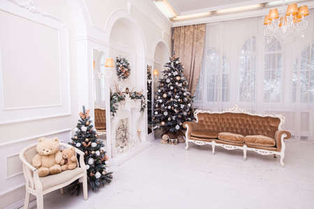 baroque room: Winter New Year and Christmas decoration in white large living room. Christmas tree with ornament near baroque sofa in classical hall.