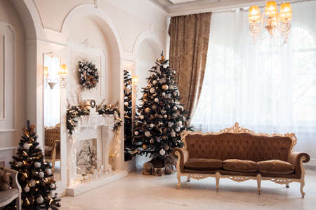 baroque room: Winter New Year and Christmas decoration in white large living room. Decorated Christmas tree near baroque sofa and classical fireplace in hall. Stock Photo