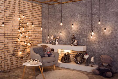 Winter loft style room decorated with original woden Christmas tree, bulbs light garland. Firewood are burning in contemporary scandinavian fireplace. Horizontal Stock Photo