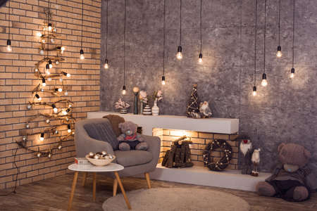 scandinavian winter: Creative wooden Christmas tree at the brick wall of Loft style room with burning bulbs garland and modern fireplace. Scandinavian winter interior of room. Horizontal