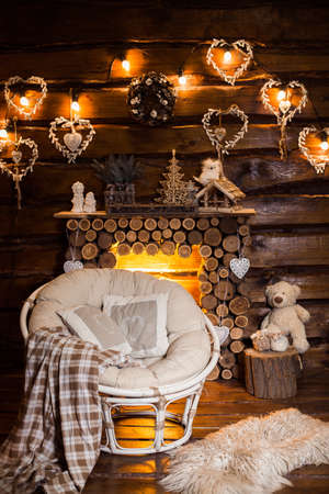 furs: Cozy papasan chair at the center of wooden room Evening bulb light garland above the wooden fireplace at the background. Holiday interior design of rustic living room. Stock Photo