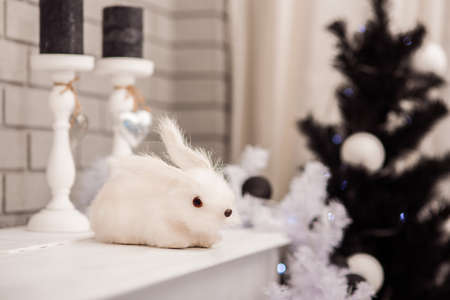 Angry rabbit with red eyes sitting on the top of piano at the black and white Christmas trees and candles