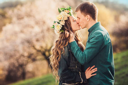 Tender kiss of young caucasian couple in sunset lights at the blossom trees background Stock Photo
