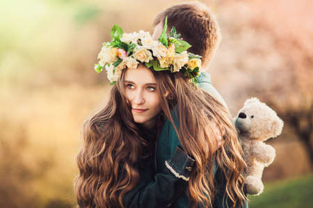 Girl with long wavy hair in a flower wreath hugging her guy. Soft background. Close-up