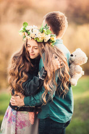 Girl with long wavy hair in a flower wreath hugging her guy. Soft background