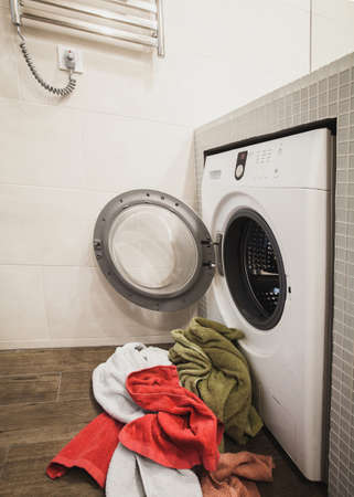 closet door: Washing machine with multicolored dirty towels on the floor near it. laundry washer with opened door. Side view. Vertical