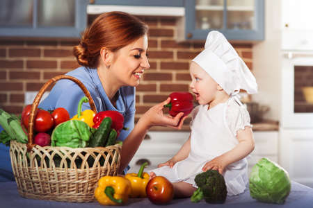 Smiling mother wearing a blue dress feeding charming one year baby girl cook. Little scullion dressed in white chef hat and apron among different vegetables. Motherhood and childhood concept. One year old child nutrition.