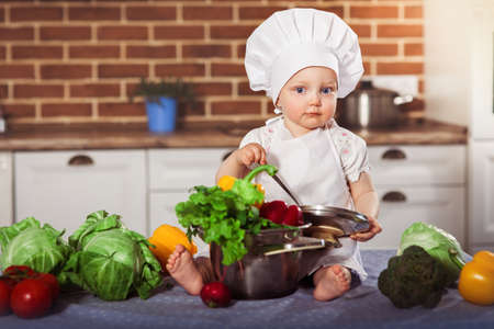 Baby girl dressed in white chef toque and apron sits with spoon near stainless pan filled by raw vegetables. Brick wall background. One year old child nutrition. Horizontal Stock Photo