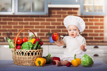 Little girl dressed in white chef hat and apron sits among vegetables and holds an apple. Brick kitchen wall at the background. One year old child nutrition. Horizontal Stock Photo