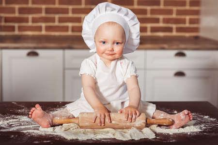 白いコック帽子とエプロンの少しの笑みを浮かべて赤ちゃん女の子パン屋は、レンガの壁の背景で生地を練り 写真素材