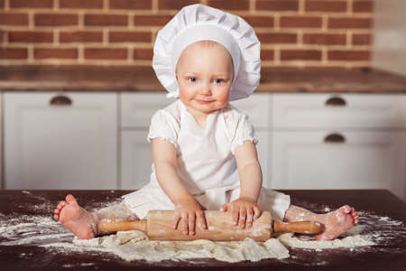 Little smiling baby girl baker in white cook hat and apron kneads a dough at brick wall background 版權商用圖片
