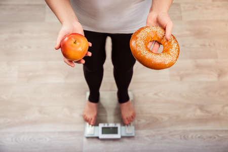 Unrecognizable slim girl checking weight on scale holding bagel and apple in her hands. Healthy nutrition concept. Weight loss and diet idea.