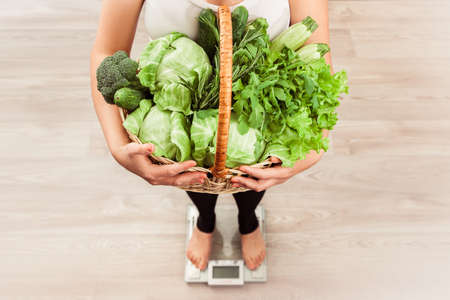 unrecognizable slim girl checking weight on scale holding basket of fresh vegetables and green meat. Weight loss and diet concept. Harmonic nutrition. Top view