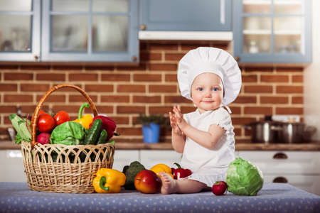 Smiling baby girl dressed in white chef toque and apron sits near wicker basket with fresh raw vegetables and applauds. Little scullion cooking in the kitchen with brick wall background. One year old child nutrition. Horizontal