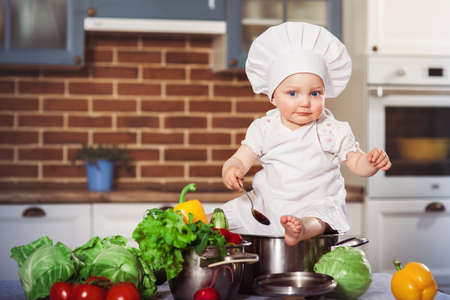 Baby girl dressed in white chef toque and apron baby sitting with spoon astride a stainless pan filled by raw vegetables. Brick wall background. One year old child nutrition. Horizontal