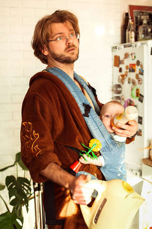 Tired young father with his newborn baby girl in a kitchen. Dad holds electric kettle and feeding his little daughter simultaneously. Stock Photo