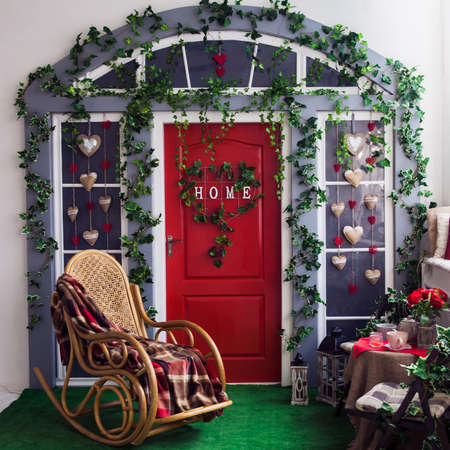 Porch with red door and climbing ivy on the wall. Wicker rocking chair at the spring terrace. Front view