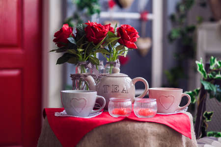 Table with vases of red rose, tea cups and teapot. Red door entrance to house Stock Photo