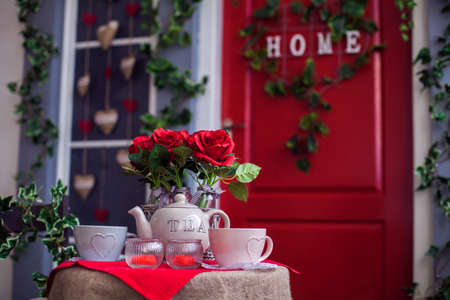 Table with vases of rose, tea cups and teapot. Red door entrance to house. Spring porch.