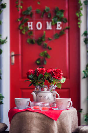 Table with vases of rose, tea cups and teapot. Red door entrance to house