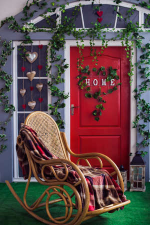 Patio with red door and climbing ivy on the wall. Wicker rocking chair at the spring terrace.