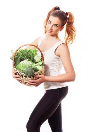 Beuatiful slim girl holding basket of fresh raw green vegetables on white background. Isolated. Stock Photo