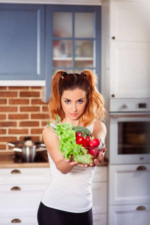 Beautiful thin girl stands on modern kitchen and holding glasses bowl with ingredients for  vegetables salad. Vertical Stock Photo