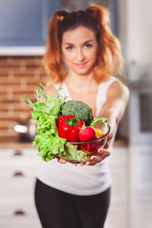 Beautiful caucasian girl holding glasses bowl with ingredients for low-caloric vegetables salad on kitchen. Selective focus. Vertical Stock Photo