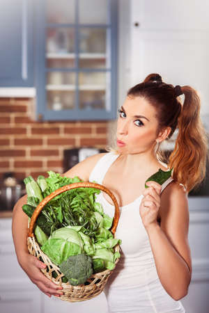 Beatiful caucasian girl in sporty wear holding basket of fresh vegetables and chews cucumber. Modern scandinavian style kitchen at background. Vertical