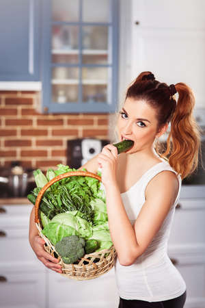 Beatiful caucasian girl in sporty wear holding basket of fresh vegetables and bites cucumber. Modern scandinavian style kitchen at background. Vertical Stock Photo