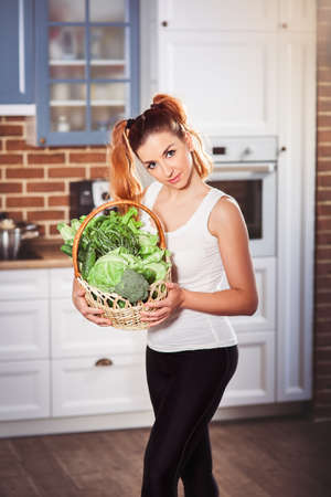 Beatiful slim girl in sporty wear holding basket of fresh vegetables on modern scandinavian style kitchen background. Vertical Stock Photo