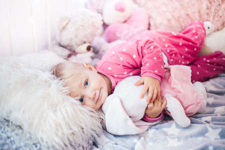 smiling caucasian baby girl lying on a fur pillow and embracing a plush bunny