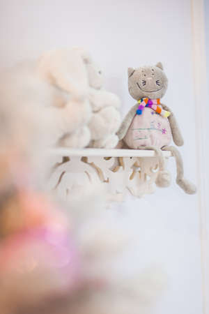 Smiling plush cat toy sits with dangling legs on white rack
