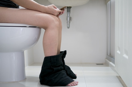 defecate: A Woman sitting on the toilet with smartphone.