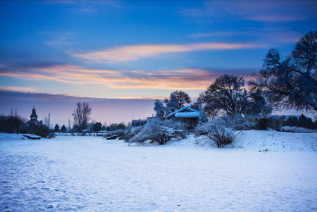 Farmhouse with snow during sunset