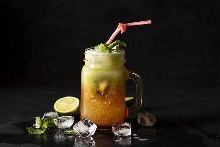 cocktail de kiwe avec de la glace, en pot Mason avec panorama de garniture à la menthe et limon, sur baground noir. - Image