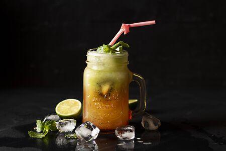 cocktail di kiwi con ghiaccio, in barattolo con contorno di menta panorama e limon, su fondo nero. - Immagine