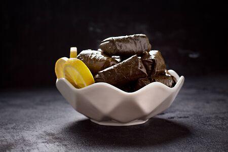 Stuffed vine leaves served on a restaurant plate, on black backround - Image Imagens