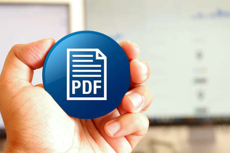 PDF document icon blue round button holding by hand infront of workspace background closeup business concept