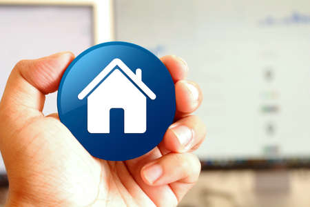 Home icon blue round button holding by hand infront of workspace background closeup business concept