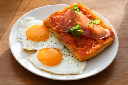Bruschetta with olive oil, tomato, ham and eggs photo