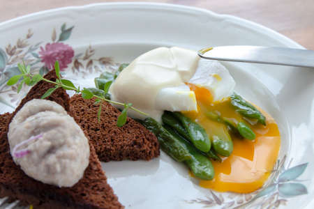 eating pastry: Green beans topped with poached egg close view Stock Photo