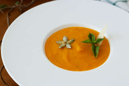 dietary: Pumpkin soup in white modern plate, dietary vegetable soup.