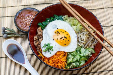 alimentos y bebidas: bibimbap en un bol, plato coreano en estera de bambú Foto de archivo