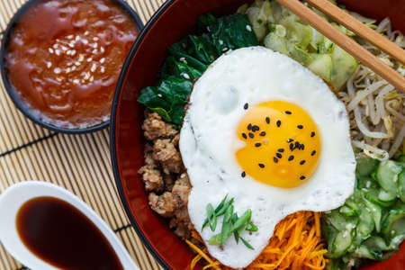 Korean cuisine, beef  Bibimbap in  a clay pot on bamboo